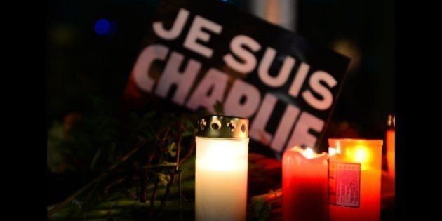 Candles and flowers are placed in front of a poster reading 'I am Charlie' during a spontaneous vigil...
