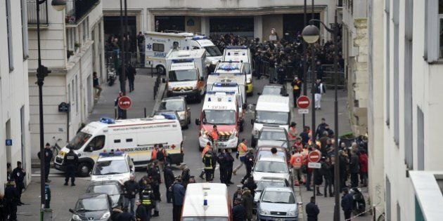 A general view shows firefighters, police officers and forensics gathered in front of the offices of...