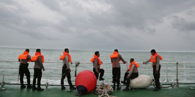 Indonesian police stand on the deck of a National Search And Rescue Agency (BASARNAS) ship during a search...