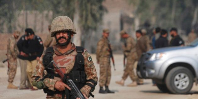 Pakistani army soldiers cordon off the area of a bombing in Peshawar, Pakistan Friday, Nov. 21, 2014....