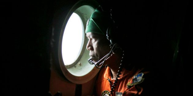 A crew of an Indonesian Air Force C-130 airplane of the 31st Air Squadron looks out of the window during...