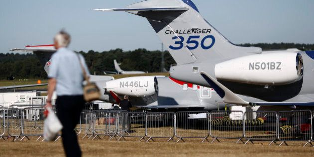 A visitor passes a Bombardier Challenger 350 business aircraft, produced by Bombardier Inc., as it stands...