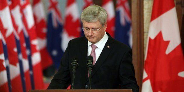 Canadian Prime Minister Stephen Harper pauses as he address the media alongside Australian Prime Minister...