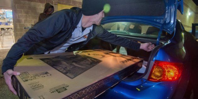 A Best Buy employee helps a customer load a new big screen TV into his car shortly after the Black Friday...