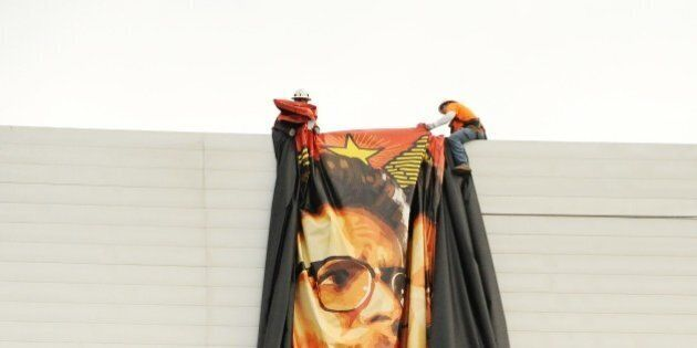 Workers remove a poster- banner for 'The Interview' from a billboard in Hollywood, California, December...
