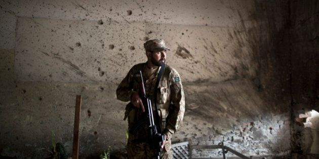 A Pakistani army officer, stands in front of a wall riddled with bullet marks, inside the Army Public...
