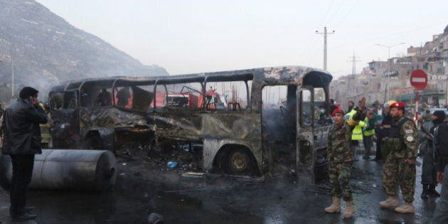 Afghan security guards inspect a damaged bus at the site of a suicide attack by the Taliban in Kabul,...