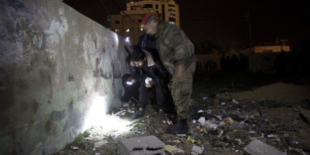 Palestinian police inspect a damaged wall of the French Cultural Center in Gaza City on December 12,2014...