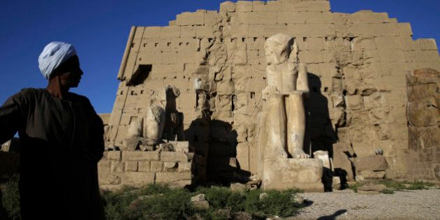 An Egyptian tourist guide waits tourists in at the ruins of the Karnak Temple in Luxor, Egypt, Sunday,...