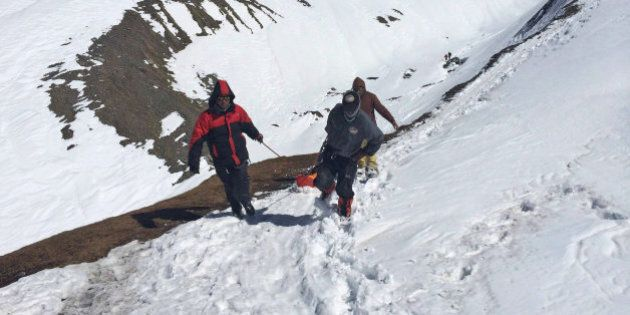 In this handout photo provided by the Nepalese army, rescue team members carry the body of an avalanche...
