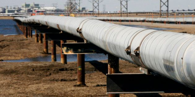 FILE - In this 2007 file photo, a new oil transit pipeline runs across the tundra to flow station at...