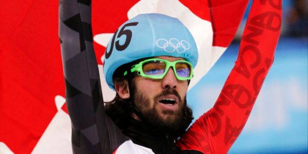 Charles Hamelin of Canada celebrates with the national flag after winning the men's 1500m short track speedskating final at the Iceberg Skating Palace during the 2014 Winter Olympics, Monday, Feb. 10, 2014, in Sochi, Russia. (AP Photo/Bernat Armangue)