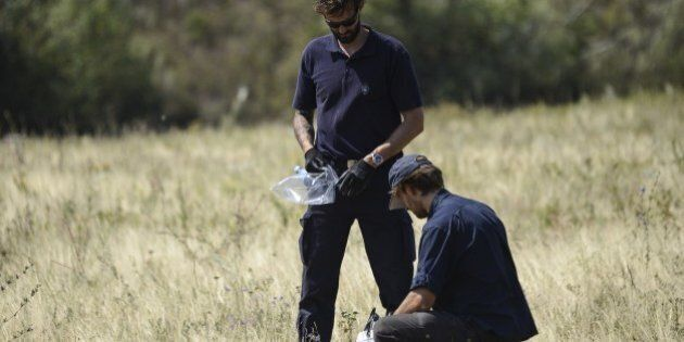 Dutch experts collect evidence as they examine the area of the Malaysia Airlines Flight 17 plane crash...