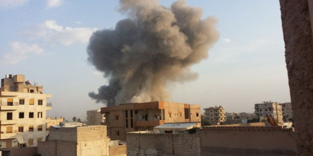 RAQQA, SYRIA - NOVEMBER 25 :  Smoke rises after air strikes by Syrian army  warplanes on the ISIL-held northern city of Raqqa, Syria on November 25, 2014. At least 130 people have been killed when Syrian war planes struck in Raqqa. (Photo by Stringer/Anadolu Agency/Getty Images)