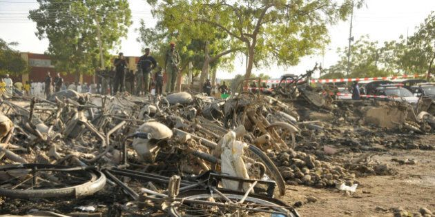 Police officers stand by the debris following an explosion in a Mosque in Kano, Nigeria, Friday Nov....