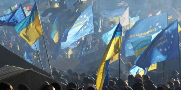 Protesters wave European Union and Ukrainian flags during a rally of the Ukrainian opposition on December...