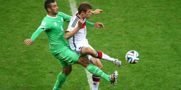 PORTO ALEGRE, BRAZIL - JUNE 30: Essaid Belkalem of Algeria challenges Thomas Mueller of Germany during...