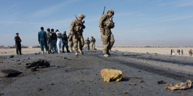 US soldiers, with Afghan policemen, inspect the site of a suicide attack targeting foreign troops in Jalalabad on November 13, 2014. A suicide bomber rammed his explosive-laden vehicle into an armoured vehicle of foreign forces in Jalalabad, the capital of eastern Nangarhar province on November 13, officials said. The attack caused no fatalities to foreign forces or civilians, but damaged an armoured vehicle.   AFP PHOTO/Noorullah Shirzada        (Photo credit should read Noorullah Shirzada/AFP/Getty Images)