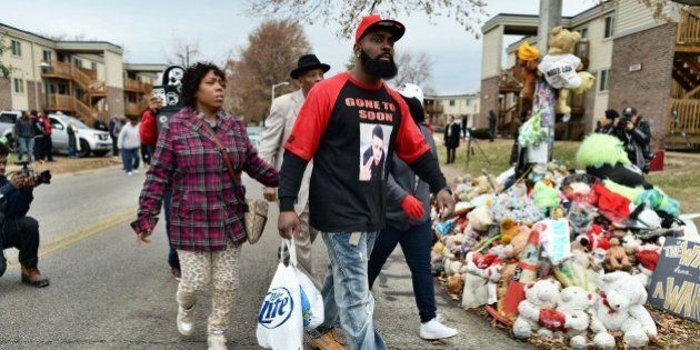 Michael Brown Sr. (C), the father of 18-year-old Michael Brown who was shot dead by a police officer, distributes turkey for Thanksgiving to neighbors where his son was killed in Ferguson, Missouri, on November 22, 2014. Tensions rose Saturday in the troubled St Louis suburb of Ferguson, with a grand jury poised to decide whether to prosecute a white police officer for killing an unarmed black teenager. US President Barack Obama has called for calm, Missouri's governor declared a state of emergency and activated the state National Guard, and the FBI has deployed an extra 100 personnel in the city.Police helicopters trained search lights over Ferguson late Friday as a small gaggle of protesters braved the cold to demand that officer Darren Wilson stand trial for shooting 18-year-old Michael Brown on August 9. AFP PHOTO/Jewel Samad        (Photo credit should read JEWEL SAMAD/AFP/Getty Images)