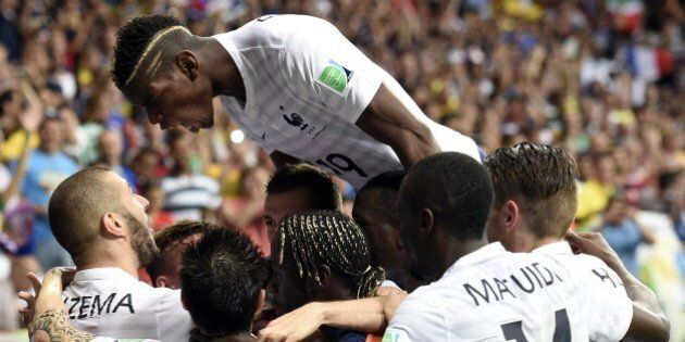 France's forward Karim Benzema (L) celebrates with teammates after scoring during a Group E football...