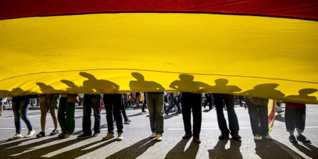 BARCELONA, SPAIN - OCTOBER 12: Anti-independence Catalan protestors hold a big Spanish flag during a...