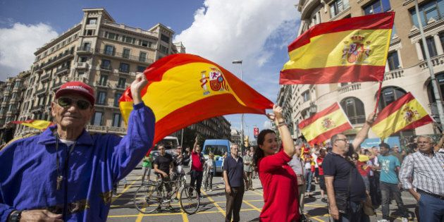 BARCELONA, SPAIN - OCTOBER 12: Anti-independence Catalan protestors carry Spanish flags during a demonstration for the unity of Spain on the occasion of the Spanish National Day at Catalunya square in Barcelona on October 12, 2014. (Photo by Albert Llop/Anadolu Agency/Getty Images)