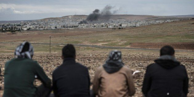 Kurdish people watch the Syrian town of Kobane, also known as Ain al-Arab, from the southeastern village...