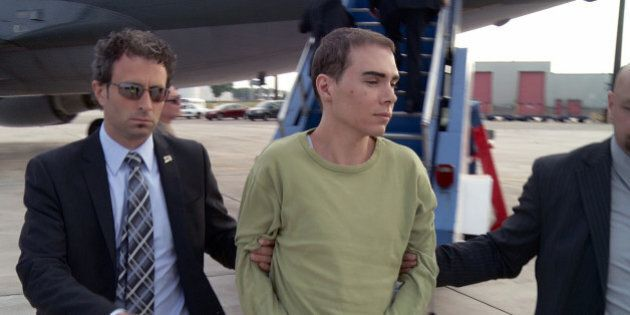 In this photo provided by Montreal Police, Luka Rocco Magnotta is taken by police from a Canadian military...