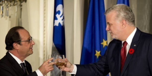 French President Francois Hollande (L) and Quebec Prime Minister Philipe Couillard (R) toast on November...