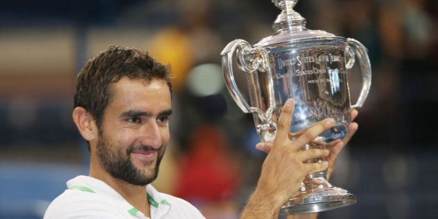 Marin Cilic, of Croatia, holds up the championship trophy after defeating Kei Nishikori, of Japan, in...