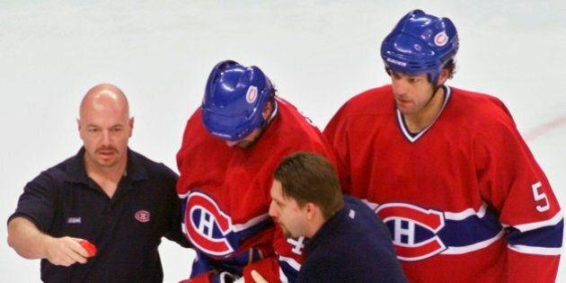 Montreal Canadiens' Sheldon Souray is taken from the ice by teammate Stephane Quintal (5) and team trainers after he was checked into the boards by Carolina Hurricanes' Jeff O'Neill during the first period of their second-round playoff game, Friday, May 3, 2002, at the Entertainment and Sports Arena, in Raleigh, N.C.(AP Photo/Karl DeBlaker)