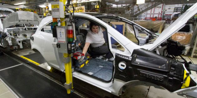 An employee works inside the chassis of an Opel Corsa automobile on the production line at the Adam Opel...