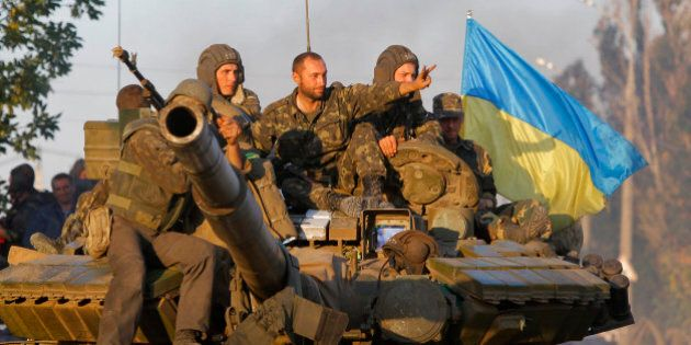 Soldiers of Ukrainian army ride on a tank in the port city of Mariupol, southeastern Ukraine, Friday,...