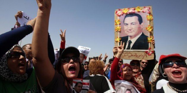 Egyptian supporters of Egyptian toppled president Hosni Mubarak (portrait) chant slogans during his trial...