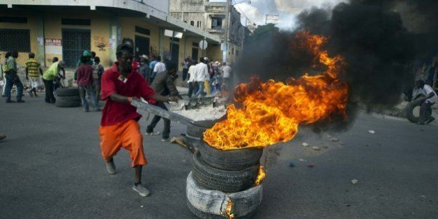 Protesters block a street with burning tires and barricades in the center of Port-au-Prince on December...