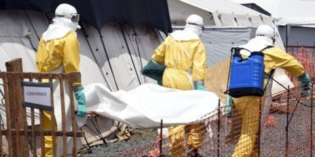 Medical staff members carry the body of a victim of Ebola, at the French medical NGO Medecins Sans Frontieres...