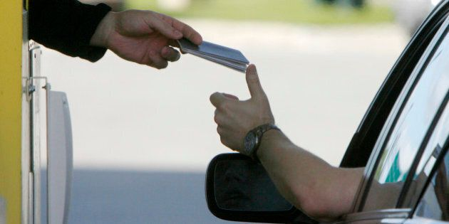 A driver hands his passport to a border agent at the U.S. border crossing in Highgate Springs, Vt., Monday,...