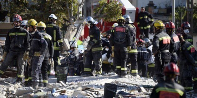 Firefighters search the rubble of a four-storey residential building which collapsed following a blast on September 01, 2014 in Rosny-sous-Bois in the eastern suburbs of Paris.  A four-storey residential building collapsed in a Paris suburb following an explosion possibly due to a gas leak, killing at least seven people, local emergency services said. Eleven people were also wounded, including four in serious condition, while 11 others are still unaccounted for.     AFP PHOTO / MARTIN BUREAU        (Photo credit should read MARTIN BUREAU/AFP/Getty Images)
