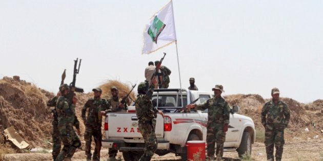 Iraqi security forces and Shiite militiamen chant anti-terrorism slogans after breaking the siege on...