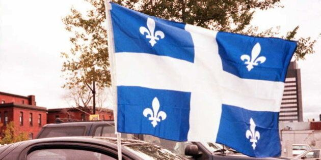 MONTREAL, CANADA: A car stopped at a street light in Montreal waves the flag of the province of Quebec...
