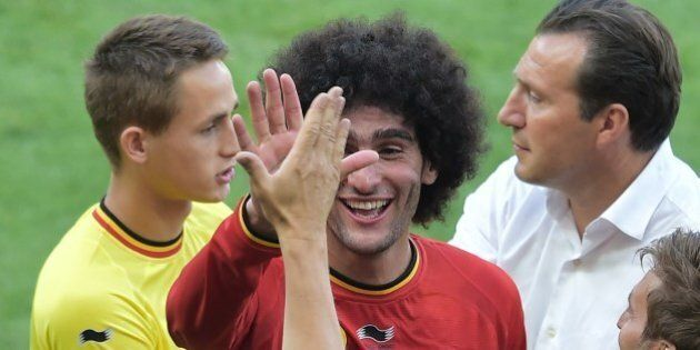 Belgium's midfielder Marouane Fellaini (2nd L) and Belgium's coach Marc Wilmots (R) celebrate after they...