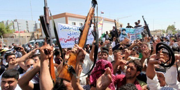 Iraqi men raise up weapons and shout slogans as they demonstration in the central Shiite Muslim shrine...