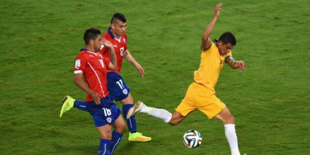 CUIABA, BRAZIL - JUNE 13: Tim Cahill of Australia is tripped up after a challenge by Gonzalo Jara (L)...