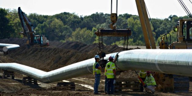 Inspectors look over the coating of a completed section of pipeline before it is lowered into a trench...