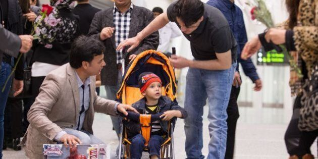 Family and well wishers shower young Abuzar Ahmad with presents and flowers as he arrives at Pearson...