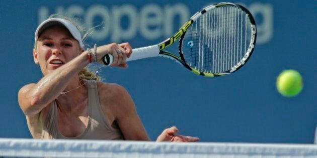 Caroline Wozniacki, of Denmark, returns a shot against Peng Shuai, of China, during the semifinals of...