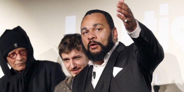 French controversial humorist Dieudonné Mbala Mbala (R) next to members of his film unit prior to the...