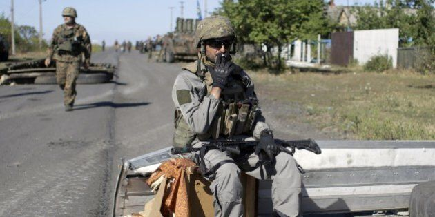 An Ukrainian serviceman smokes a cigaret during a pause in patrol on border of the Donetsk and Luhansk...