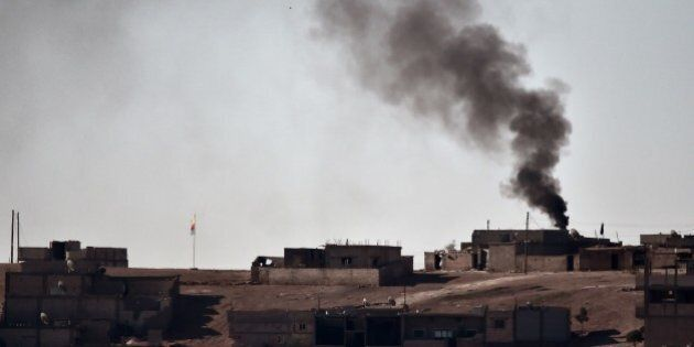 Smoke rises from the central part of the Syrian town of Ain al-Arab, known as Kobane by the Kurds, as seen from the Turkish-Syrian border, as a Kurdish flag waves during heavy fighting, in the southeastern town of Suruc, Sanliurfa province, on October 7, 2014. Pro-Kurdish protesters clashed overnight on October 7 with police in several Turkish cities, including Istanbul, in a show of anger against the lack of action by the government against jihadists fighting for a key Syrian town.   AFP PHOTO / ARIS MESSINIS        (Photo credit should read ARIS MESSINIS/AFP/Getty Images)