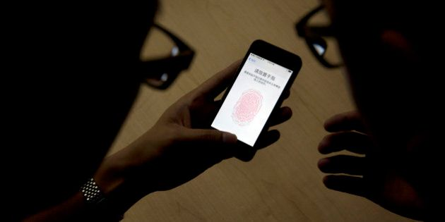 An Apple employee, right, instructs a journalist on the use of the fingerprint scanner technology built...